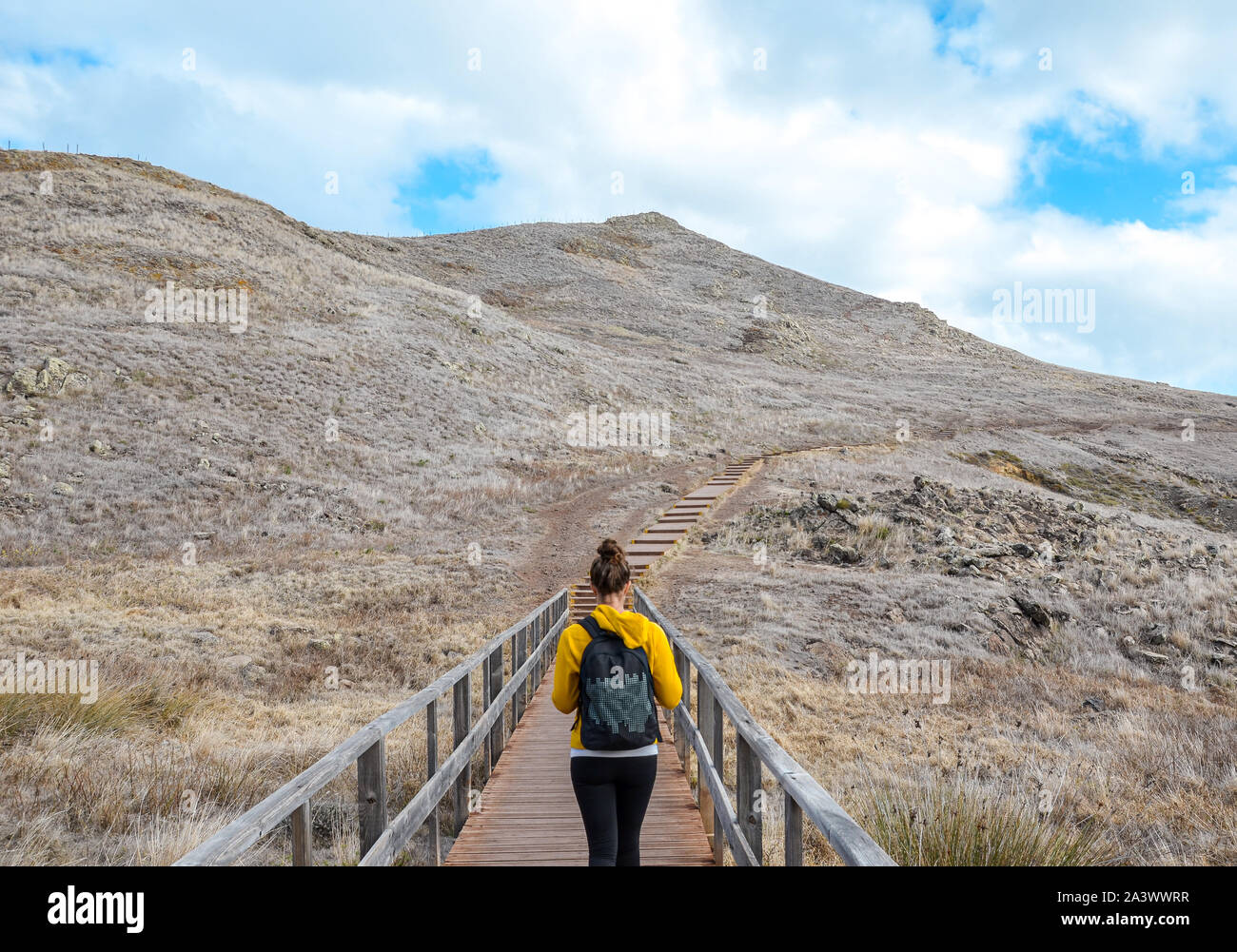 Young girl in yellow sweater on hiking path in Ponta de Sao Lourenco in Madeira, Portugal. Peninsula in eastern part of the island. Volcanic landscape. Woman traveller. Adventure concept. Stock Photo