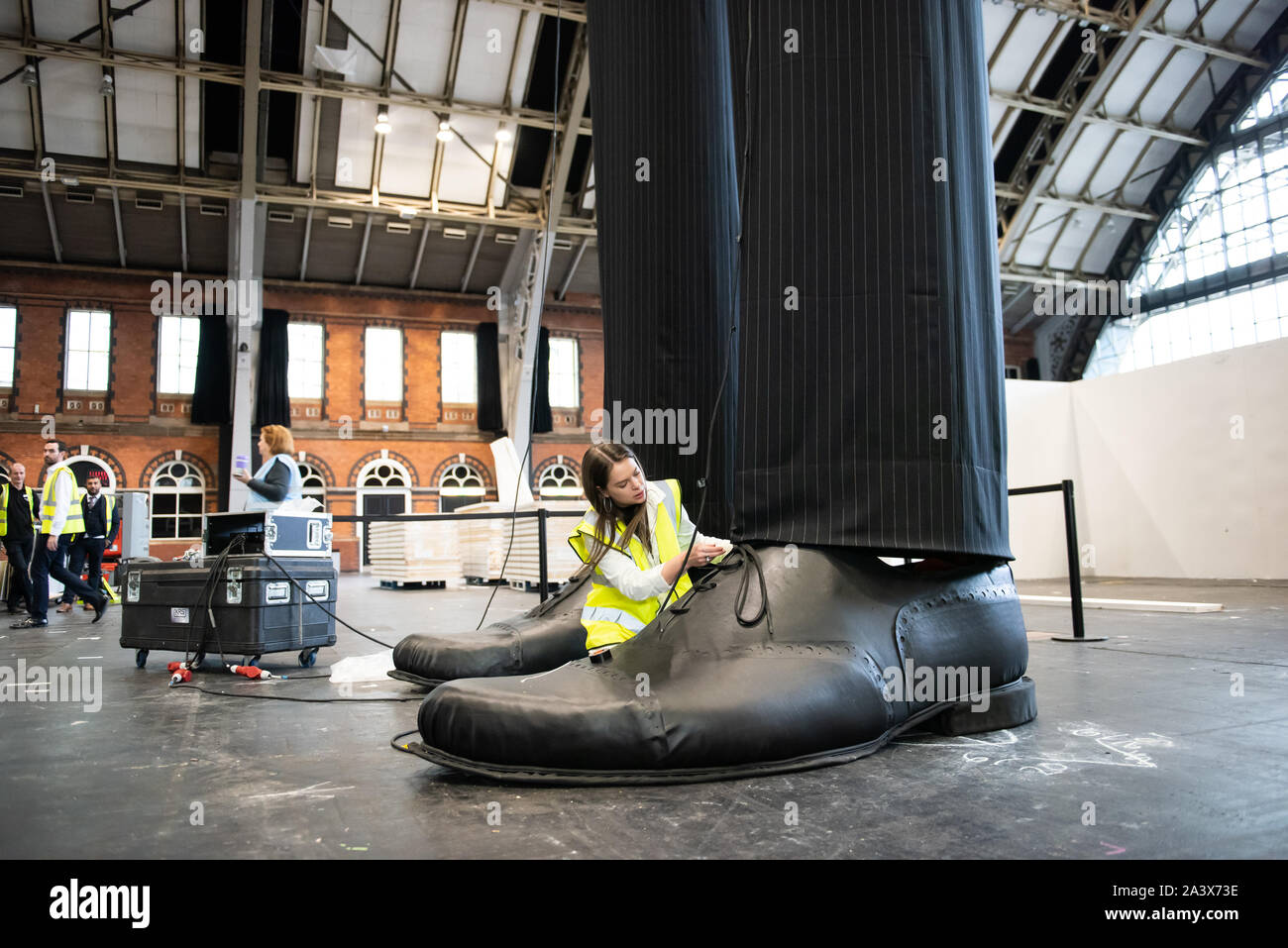 A pair of giant legs known as 'Clandestine' measuring over 10 metres in height are erected at the Aviva Investors Manchester Art Fair at Manchester Central across 11-13th October 2019. The legs are the work of 23 year old Manchester School of Art graduate Millie Sansom. The installation is made from fabric, polystyrene and faux leather and demonstrates the imbalance of power between citizens and political or corporate 'giants'. Stock Photo