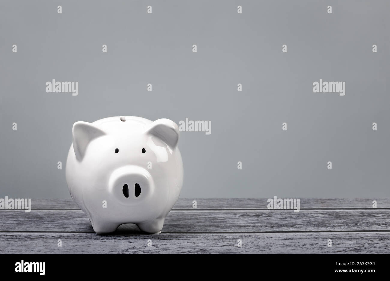 Cute white Piggy Bank over a blue and grey background. Stock Photo