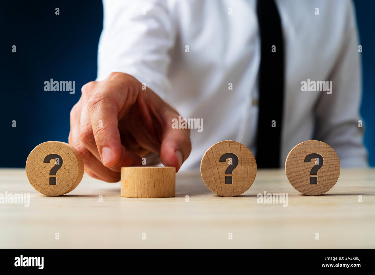 Businessman placing four wooden circles with question mark on them in a row in a conceptual image. Stock Photo