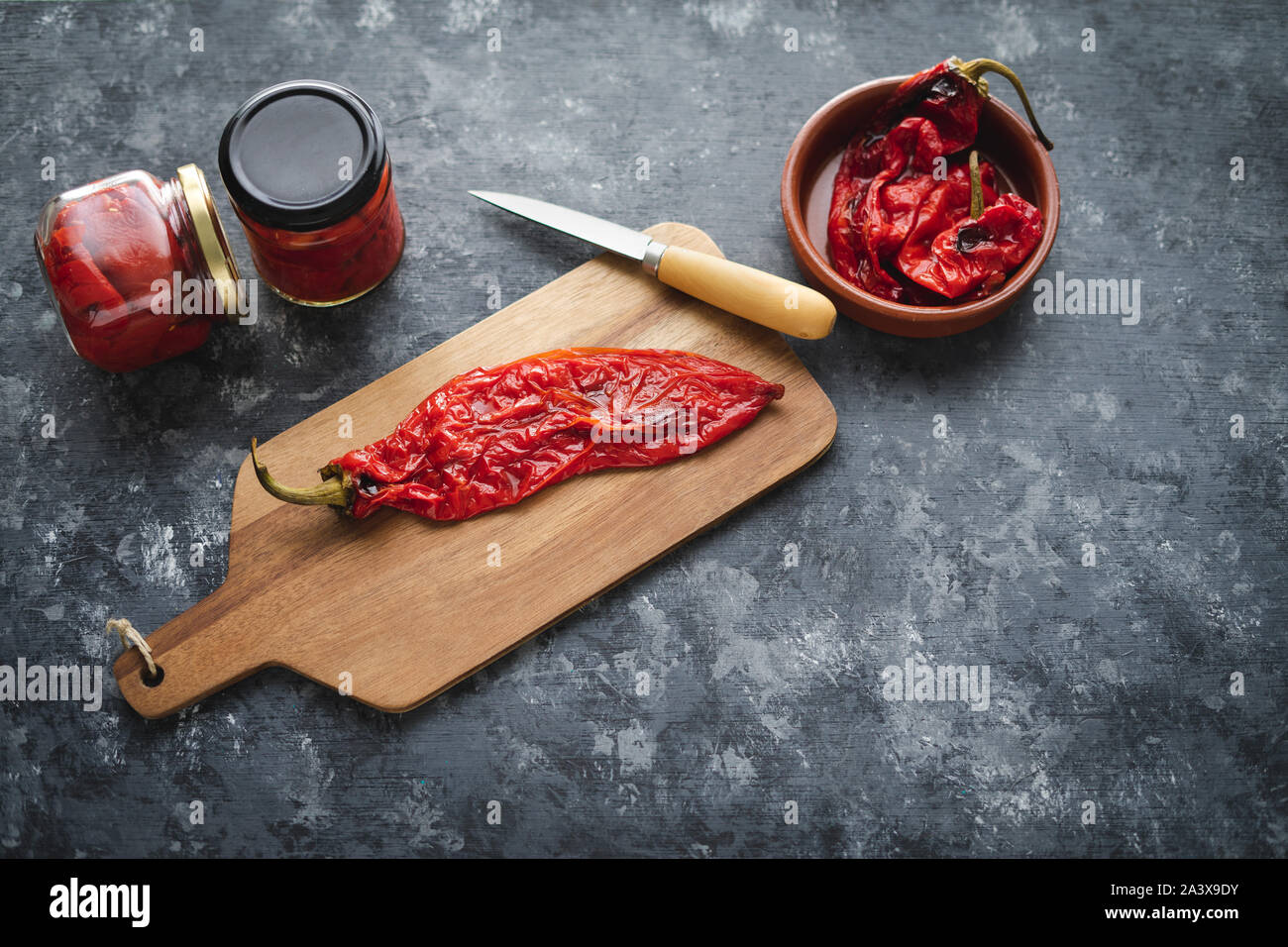 Preparing roasted red peppers for packaging. Stock Photo