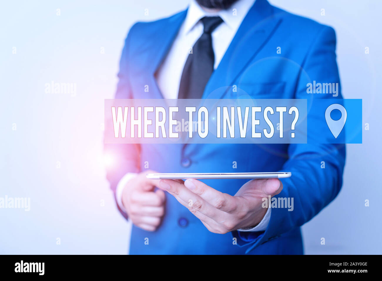 Writing note showing Where To Invest Question. Business concept for asking someone about place to put money into Businessman in blue suite with a tie Stock Photo