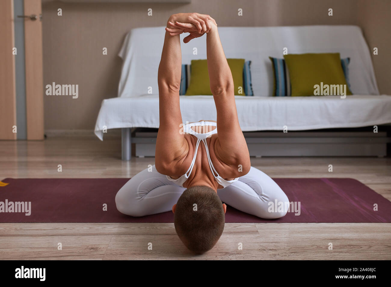Woman sit on mat with crossed legs and head down. Yogi is stretching arms up with efforts, strong muscles Stock Photo