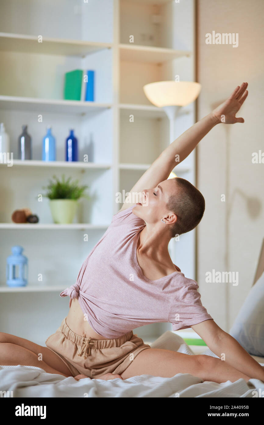 European attractive woman on bed practice yoga exercises, background white room. Hands raised up. Stock Photo