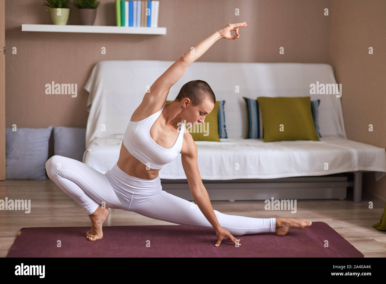 Fit caucasian woman exercising on purple mat in living room, slim and sportive body. Yoga, fitness, pilates. Athletic body of female Stock Photo