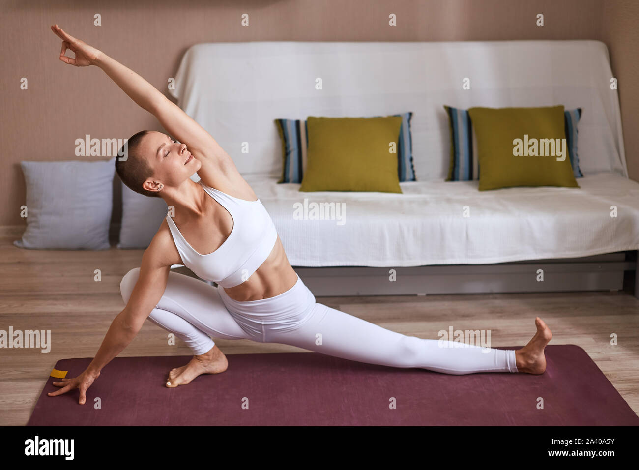 Slim young girl doing yoga exercises at home. Dressed in white leggins and topic, practice stretching. Keep muscles in tonus Stock Photo
