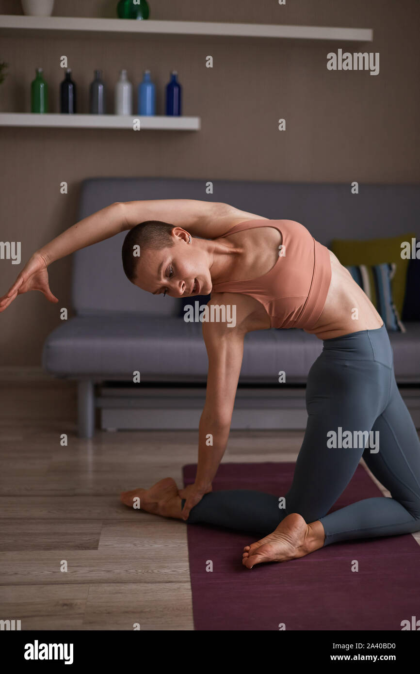 Fit caucasian woman sitting on mat and stretch muscles of body. Female practicing fitness exercises at home Stock Photo