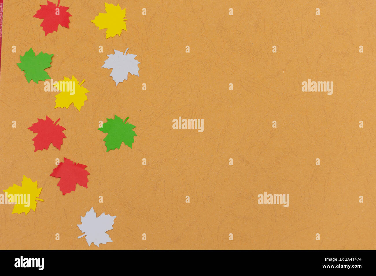 Warm fall seasonal orange  flatlay with falling festive colorful maple leaves from side on open concept and copy space availability right. Stock Photo