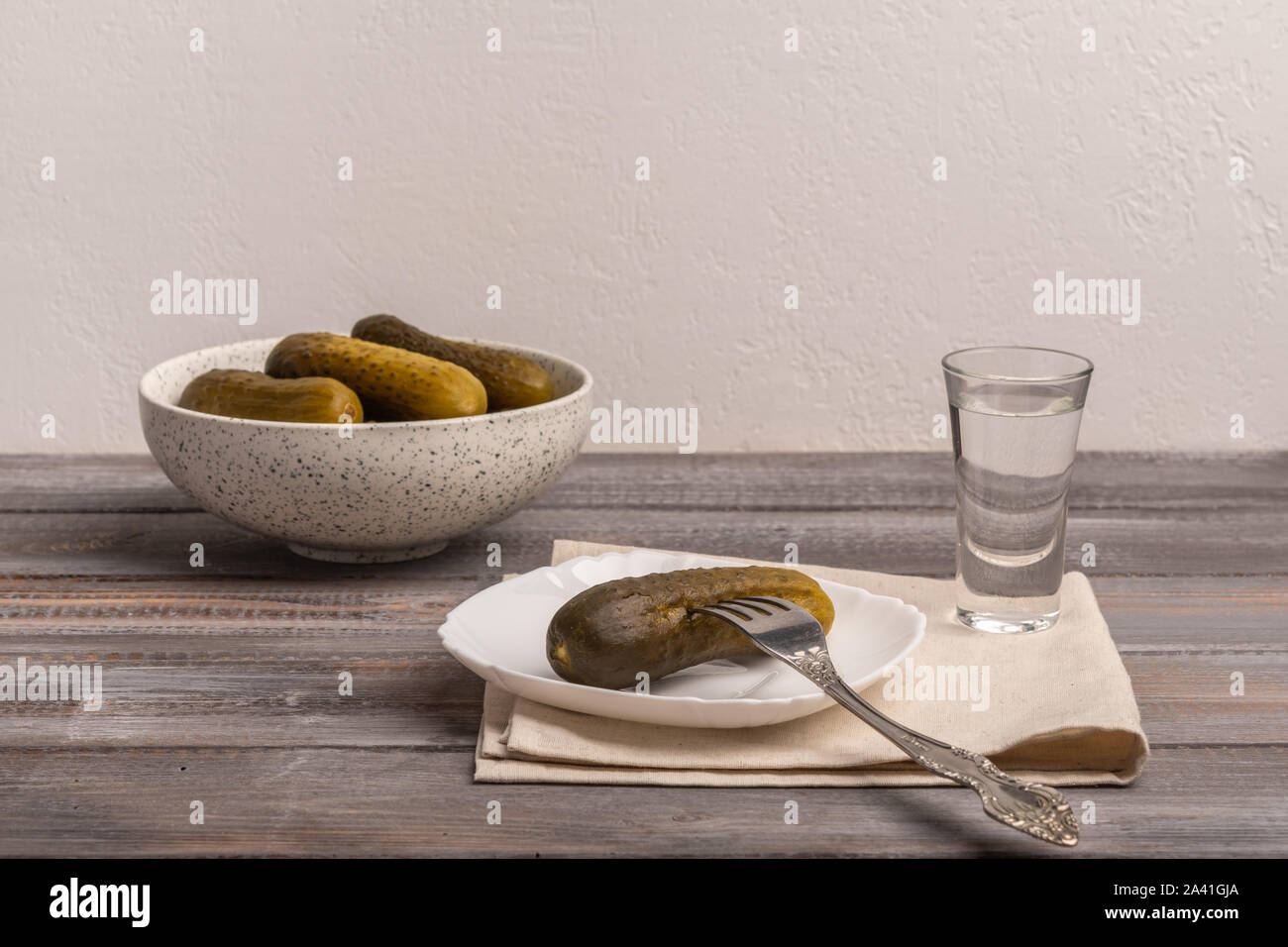 Traditional Russian snack - a glass of vodka and pickles. Rustic style Stock Photo