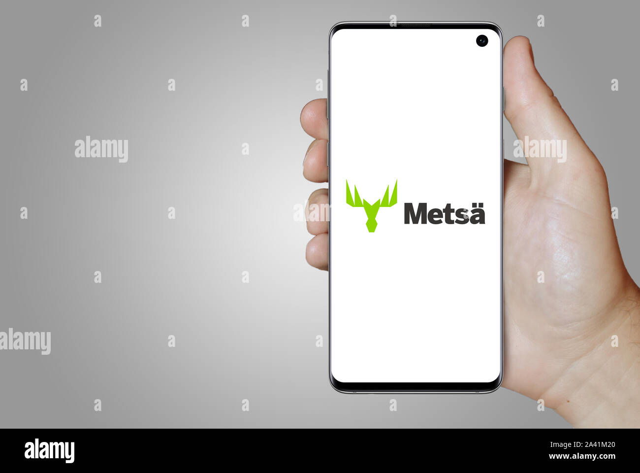 A man holds a phone displaying the logo of company Metsä Board listed on OMX Helsinki. Grey gradient background. Credit: PIXDUCE Stock Photo