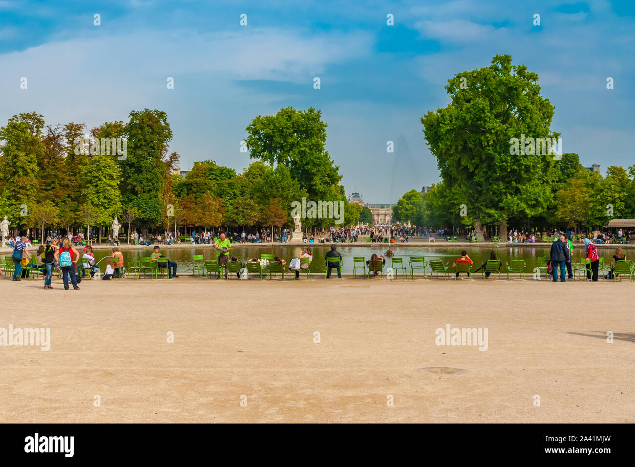 "Great panoramic view of the octagonal lake ""Bassin Octogonal"" with green chairs in the popular Tuileries Garden in Paris. Visitors celebrate, meet,... Stock Photo"