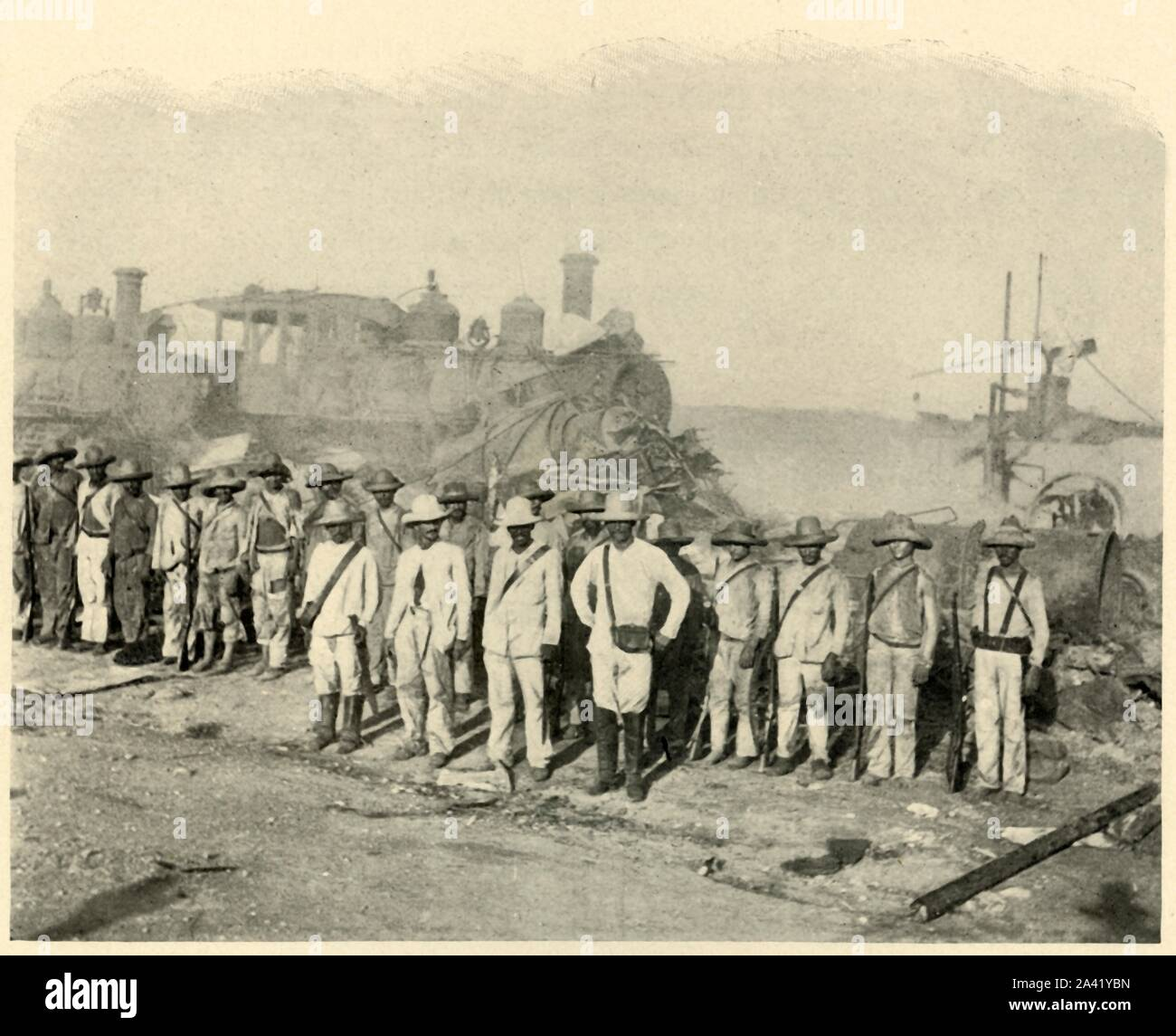"'Cuban Soldiers (?) beside Ruins of Roundhouse, Morning of June 23rd', Spanish-American War, June 1898, (1899). A group of men posing in front of steam locomotives. From ""The Little I saw of Cuba"" by Burr McIntosh, with photographs by the author. (In 1898, American actor and journalist William Burr McIntosh went to Cuba to cover the Spanish-American War for ""Leslie's Weekly"" as a reporter and photographer). [F. Tennyson Neely, London & New York, 1899] Stock Photo"