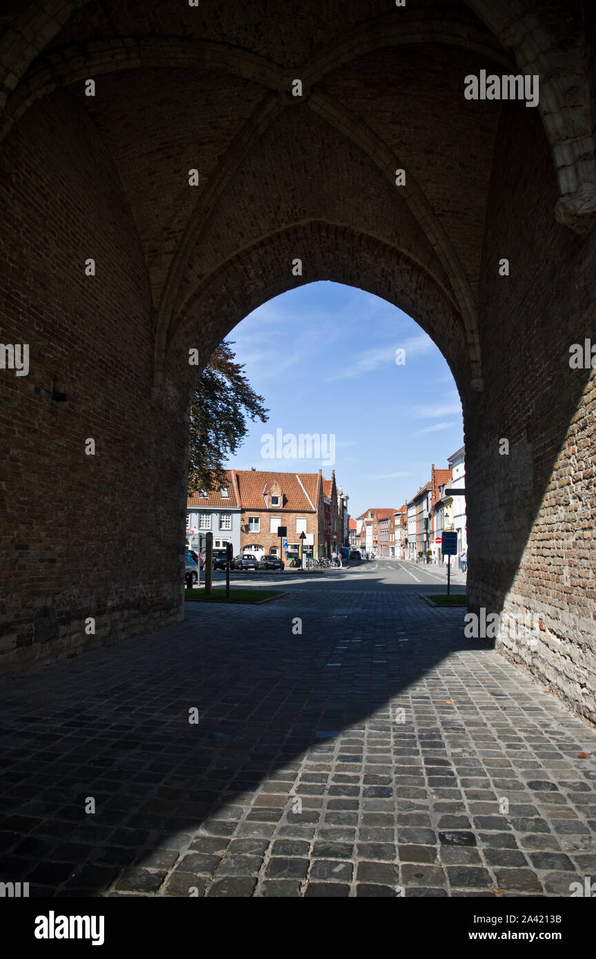 Looking through the medieval Gentpoort (Gate of Ghent) entrance to Bruges, Belgium. Stock Photo