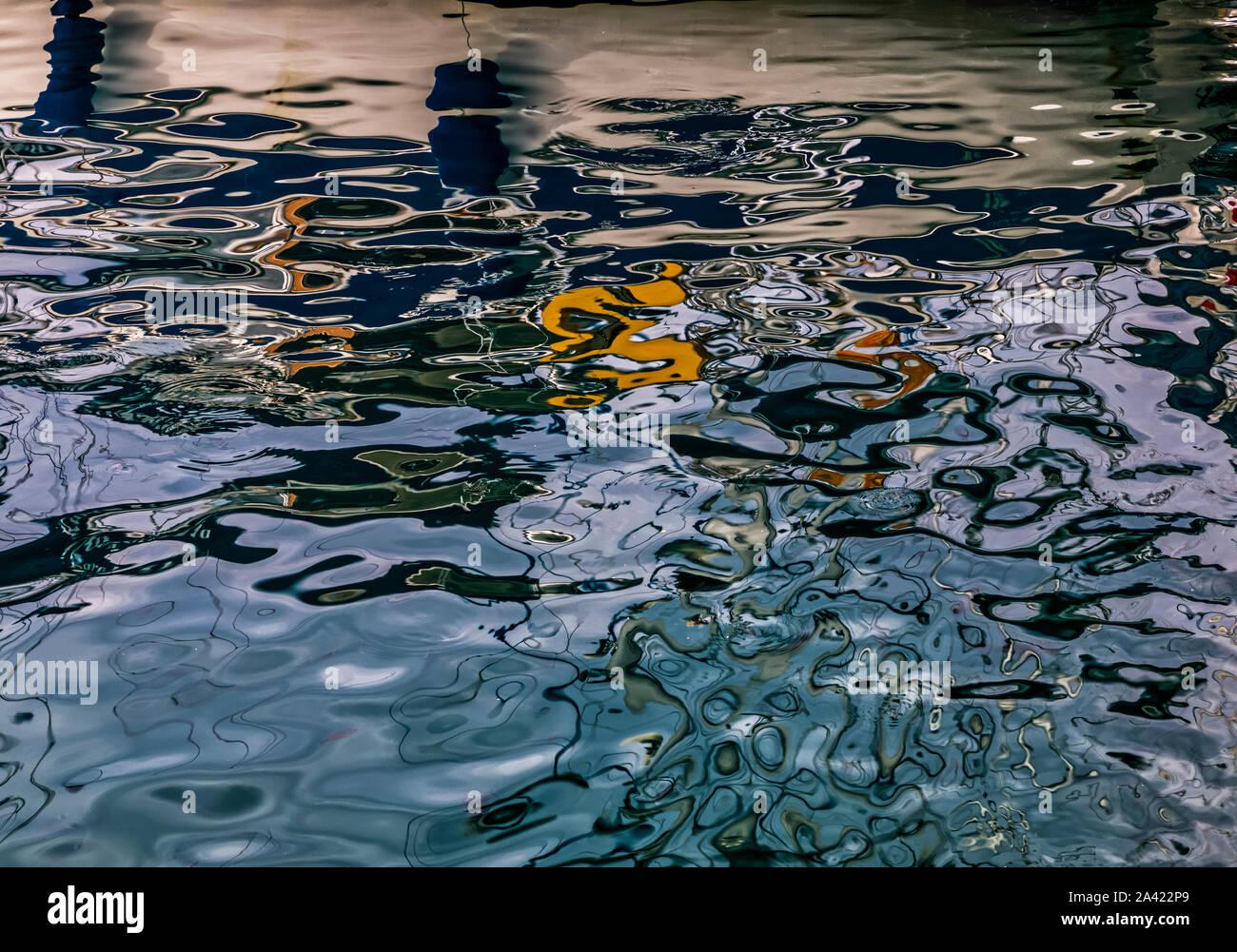 Surface of dark ripples on Aegean Sea . Interplay  of dark blue, white, and orange  reflections. Stock Image. Stock Photo