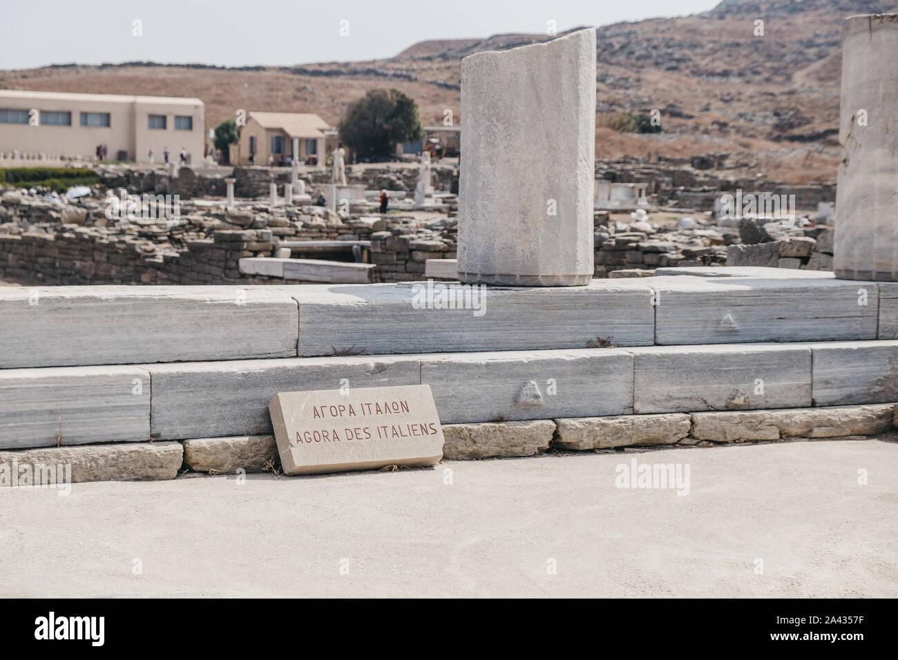 """Sign on the Agora des Italiens (""""Agora of the Italians"""") on the Greek island of Delos, archaeological site near Mykonos in the Aegean Sea Cyclades arc Stock Photo"""