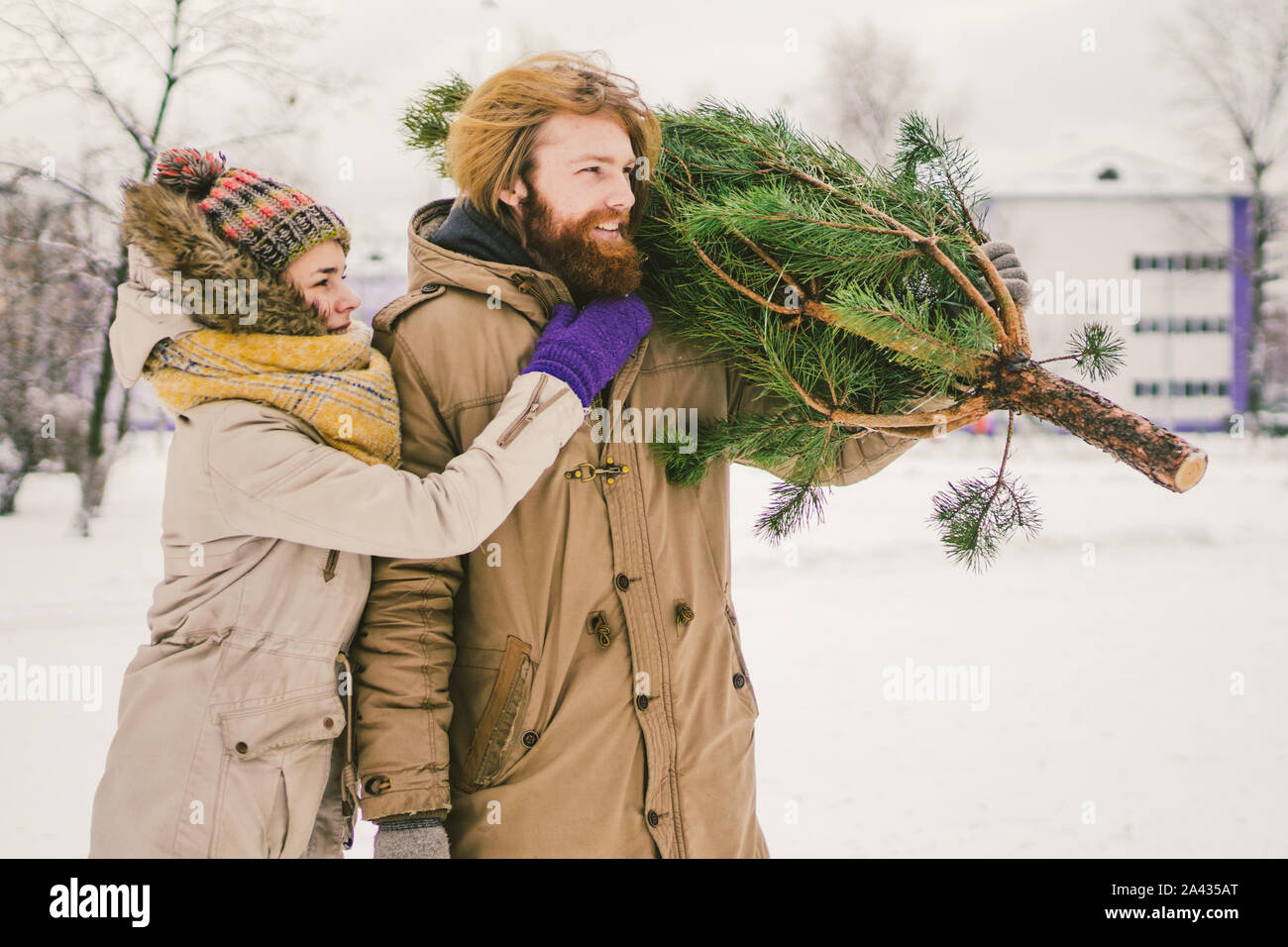 family bought Christmas tree. Buying wood in market. Bazaar. Christmas sale. Satisfied with the purchase. Family going home from Christmas shopping Stock Photo