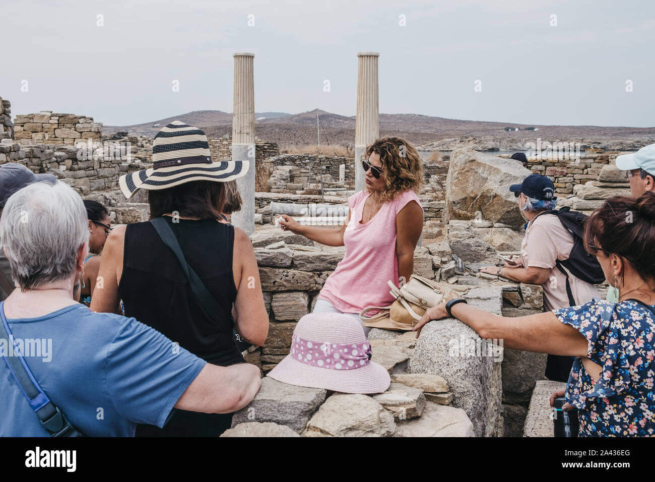 Delos, Greece - September 20, 2019: Tour guide talking to a group of visitors on the Greek island of Delos, archaeological site near Mykonos in the Ae Stock Photo