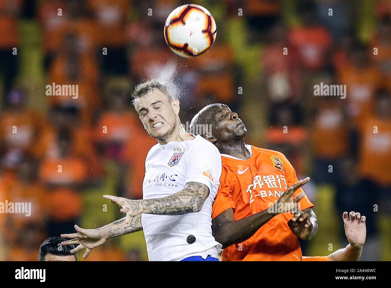 Brazilian football player Roger Krug Guedes, known as Roger Guedes, left, of Shandong Luneng Taishan heads the ball against Cameroonian football playe Stock Photo