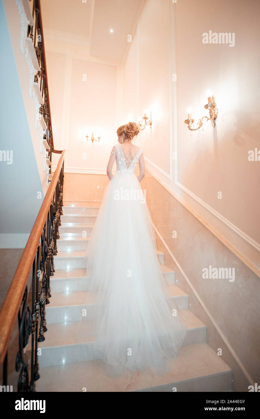 A girl in a dress climbs the stairs. Beautiful lady in a luxurious ball gown climbing the stairs. Baluster railing on both sides. Vintage concept Stock Photo