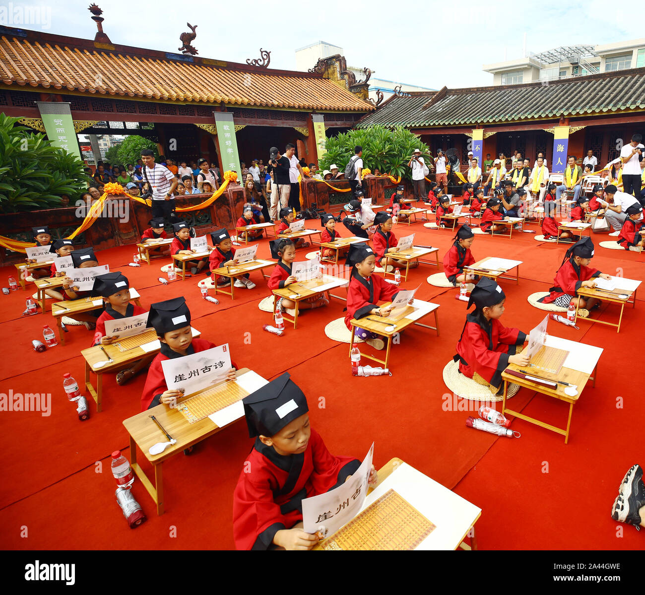 "Over 30 pre-school children dressed in traditional Han-style costumes attend their ""first writing"" ceremony at the Chinese Confucius Temple School in Stock Photo"