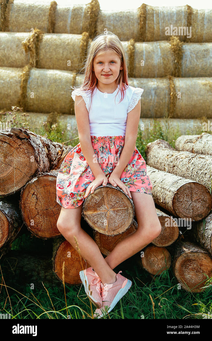 A young girl with long flowing hair sitting on a log in a pink dress Stock Photo