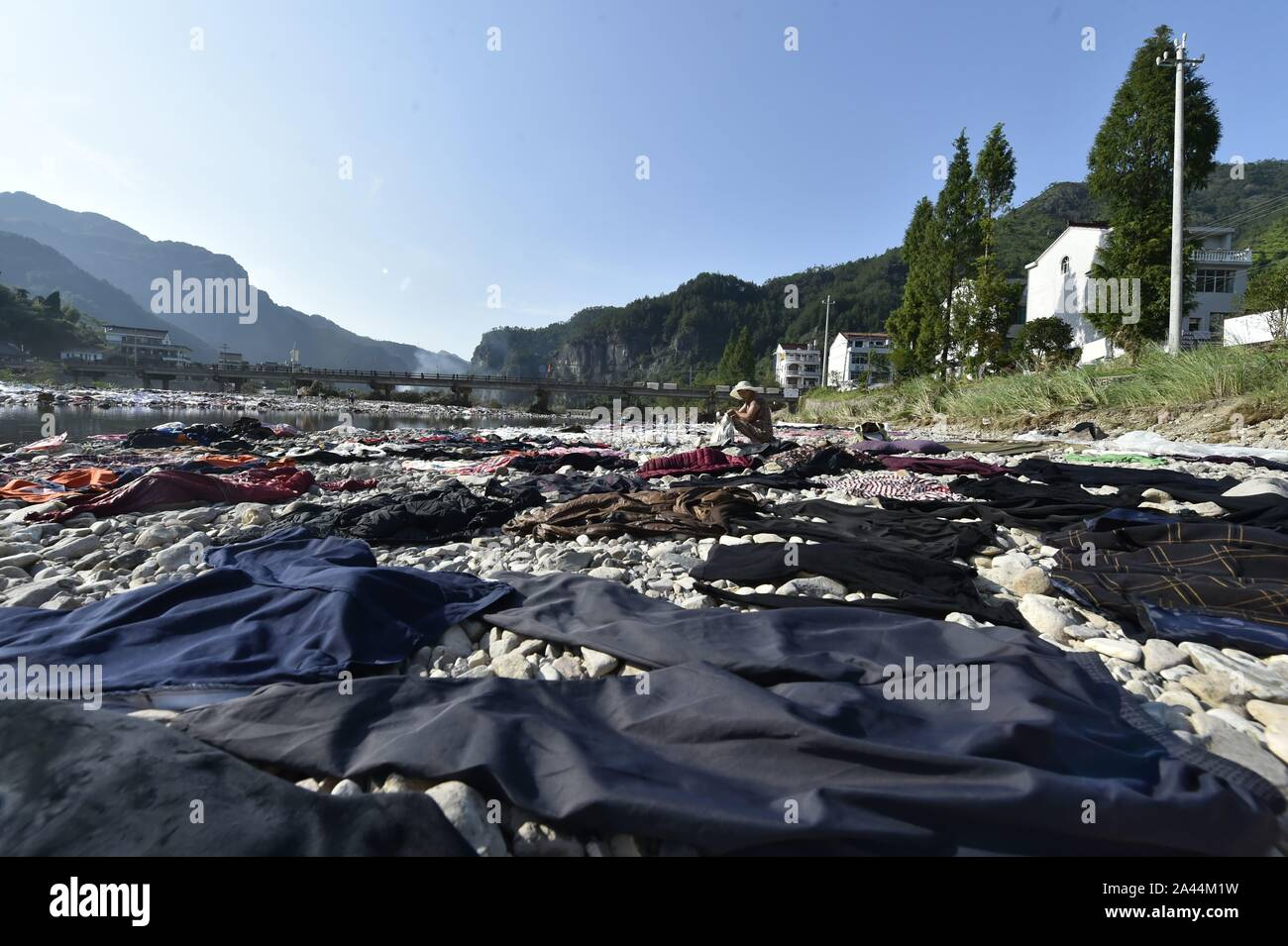 Chinese villagers put their clothes, sheets, and quilts under the sun after floodwater due to heavy rainstorm caused by the Typhoon Lekima, the 9th ty Stock Photo