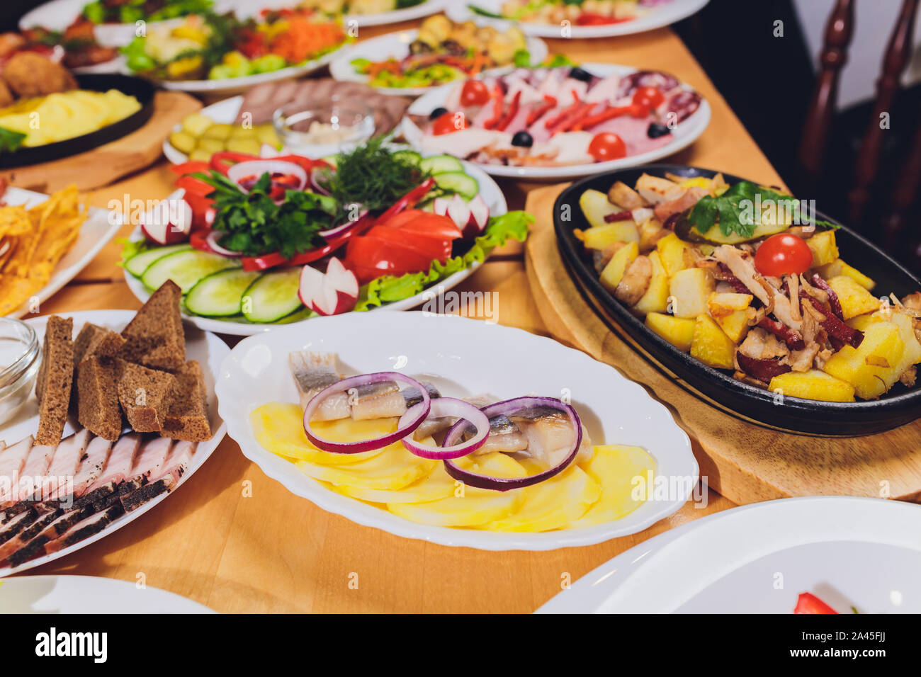 Food tray with delicious salami, pieces of sliced ham, sausage and salad. Meat platter with selection on table Stock Photo