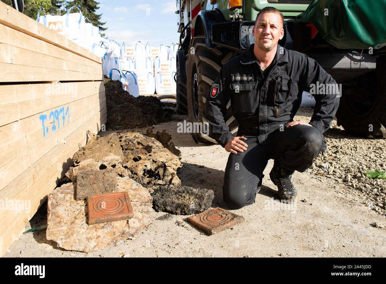 12 October 2019, Lower Saxony, Göttingen: Thorsten Lüdeke, demolition engineer of the Lower Saxony Explosive Ordnance Removal Service, sits next to remains of metal drums, slag and clay bricks found on a heap in the ground and originally suspected of being a world war bomb. In the morning about 14,000 people were evacuated around the site. Photo: Swen Pförtner/dpa Stock Photo