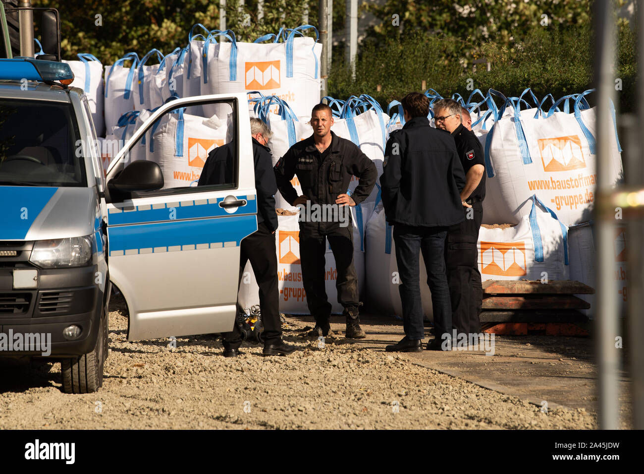 12 October 2019, Lower Saxony, Göttingen: Thorsten Lüdeke (M), demolition engineer of the Lower Saxony Explosive Ordnance Removal Service, stands with colleagues at the site where the remains of metal drums, slag and clay bricks were found, which were found on a heap in the ground and were originally suspected as a world war bomb. In the morning about 14,000 people were evacuated around the site. Photo: Swen Pförtner/dpa Stock Photo