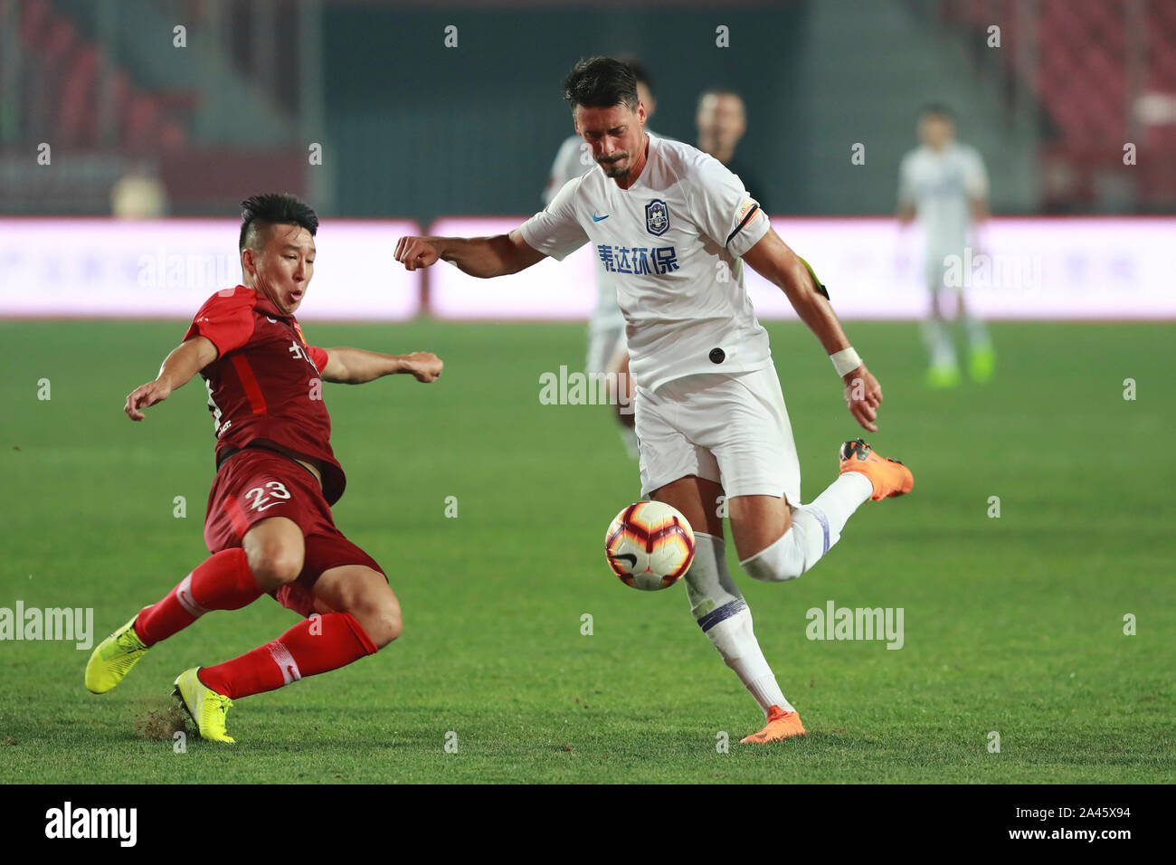 German football player Sandro Wagner of Tianjin TEDA F.C., right, keeps the ball during the 25th round match of Chinese Football Association Super Lea Stock Photo