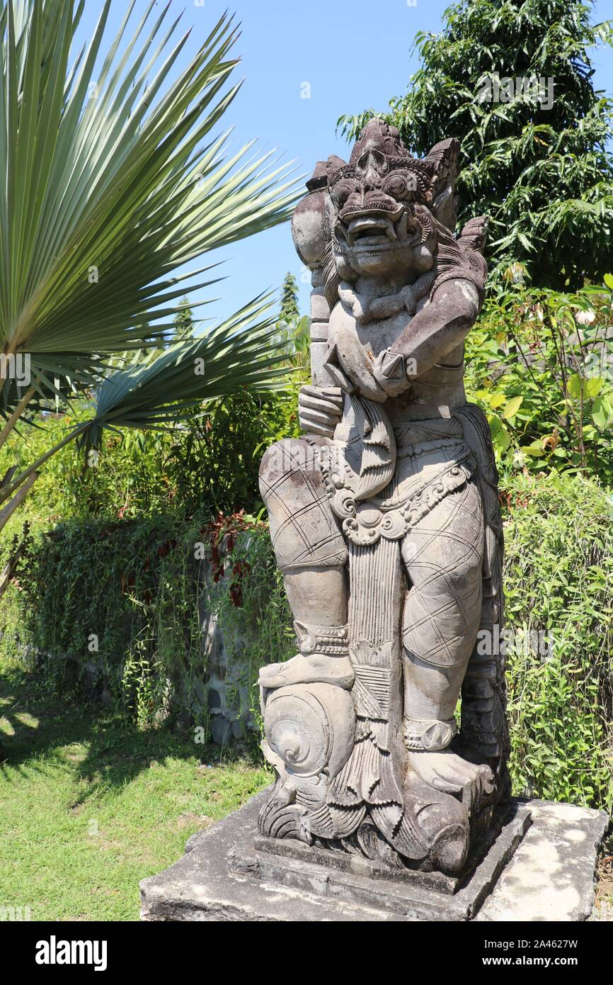 Statue Of White Stone In Tropical Garden Among Flowers On Bali