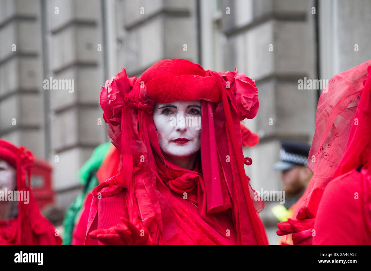 London, UK. 11 October 2019. Red-robed, Climate change protesters, The Red Brigade, from Extinction Rebellion walk along Whitehall in London. By day 5 protestors, still occupied Trafalgar Square despite many of their campsites around Westminster being removed by police. One of Extinction Rebellion's main demands is to reduce greenhouse gases to net zero by 2025. Over 1,000 arrests were made in the first week. 500 officers were drafted in from around England and Wales to help support the Metropolitan police. Stuart Walden / Alamy Stock Photo