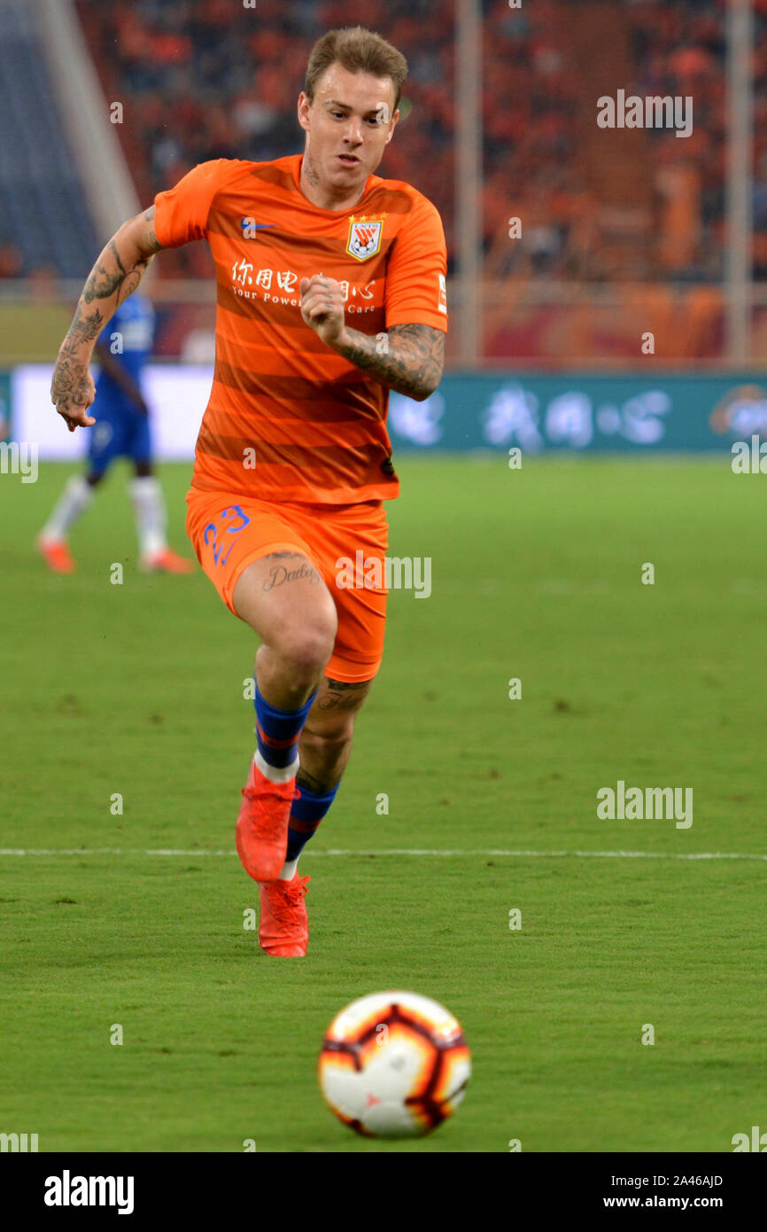 Brazilian football player Roger Krug Guedes, known as Roger Guedes, of Shandong Luneng Taishan F.C. chases after the ball during the 25th round match Stock Photo