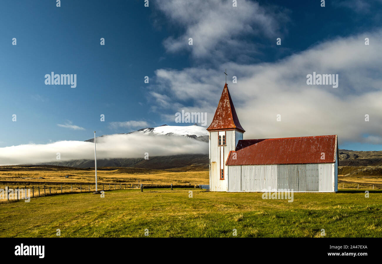 Disused Icelandic Church at Hellnar with white walls and a red roof and spire on the Snaefellsnes Iceland Stock Photo