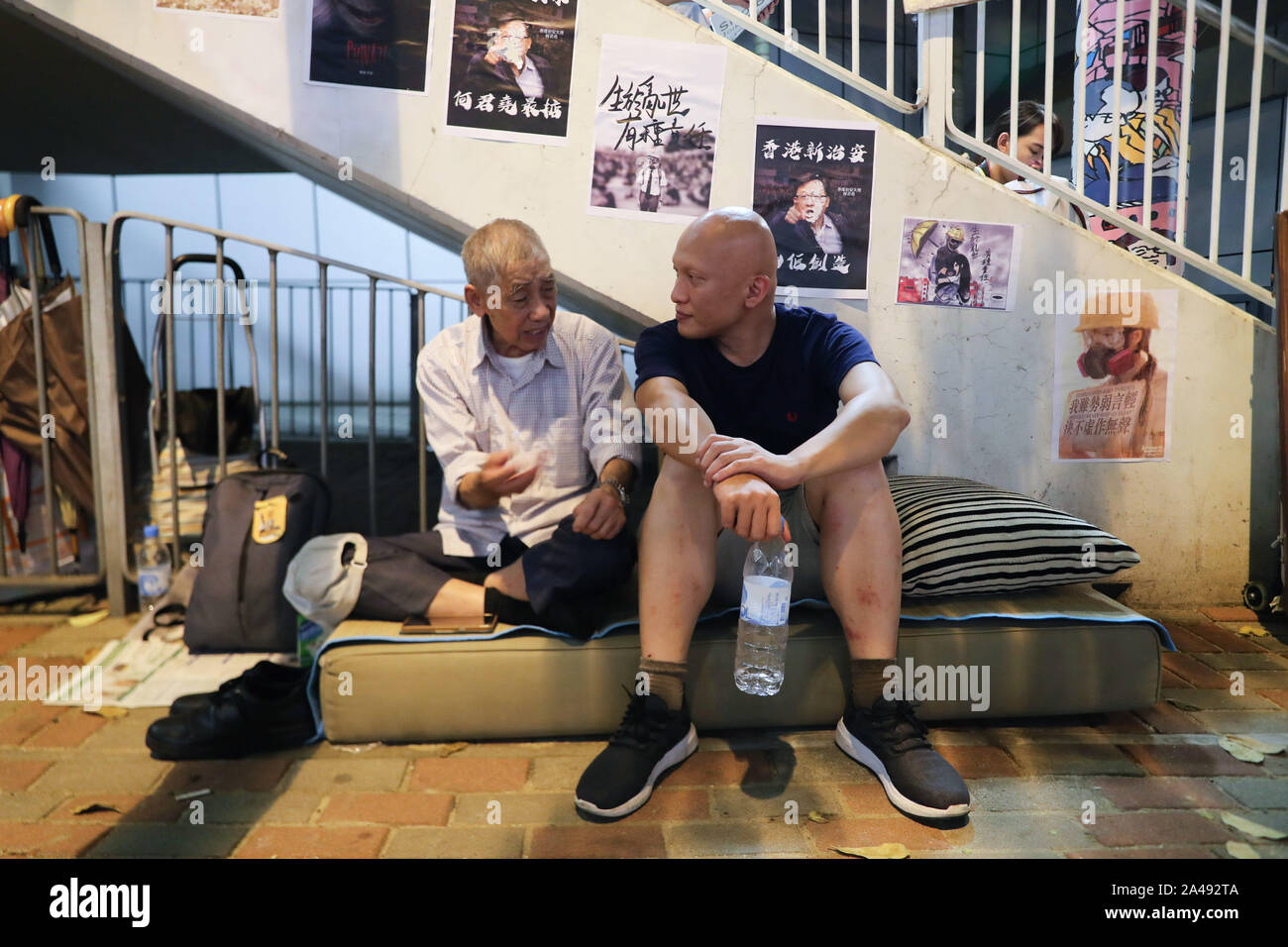 Hong Kong, China. 12th Oct, 2019. Two seniors chatting outside police headquarters during the protests.Hong Kong Protests continue for the 5th month. More demonstrations and rallies have taken place including the silver hair, a 48 hours strike of sitting peacefully outside police headquarters. Credit: SOPA Images Limited/Alamy Live News Stock Photo