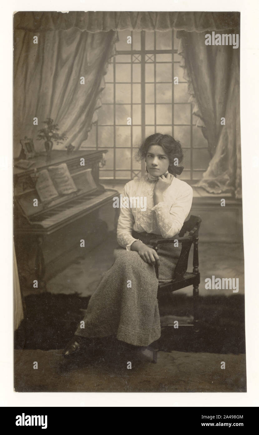 Edwardian studio portrait, cut down postcard of pretty young woman or late teens girl seated by piano prop, wearing high necked lace blouse and woollen skirt, circa 1910, 1911, U.K. Stock Photo