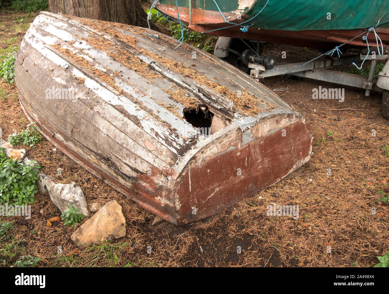 Old wooden row boat with a hole in its hull Stock Photo