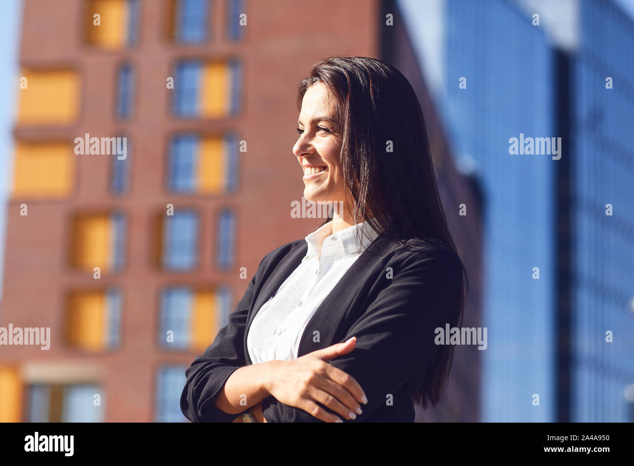A happy businesswoman is smiling on the background of a business building outdoors. Stock Photo