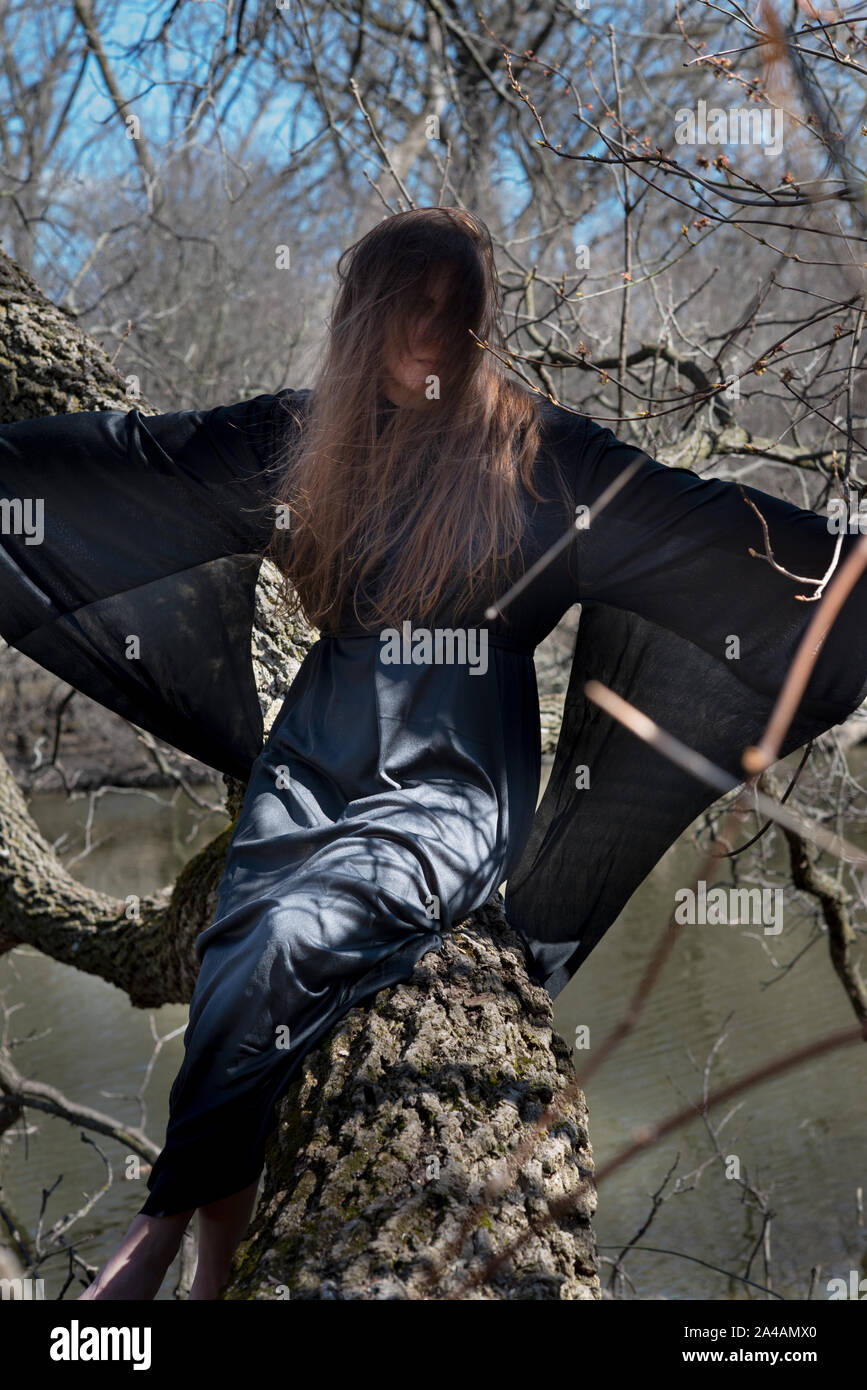 Woman With Dark Long Hair In Black Robes Hanging On Tree Branches In The Middle Of A Swamp Halloween And Gothic Concept Witchcraft And Magic Witch Stock Photo Alamy