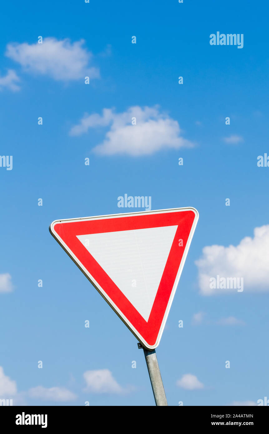 Single triangle road sign in red and white, give way, against blue sky and clouds Stock Photo