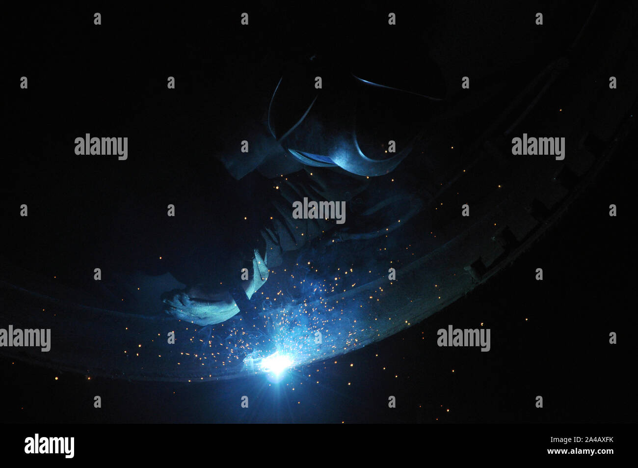 Professional welder welds an industrial tank in a workshop. Stock Photo