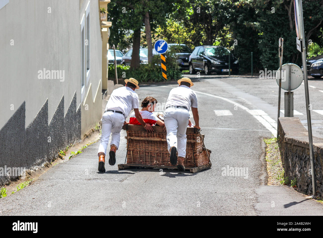 Monte, Madeira, Portugal - Sep 14, 2019: Toboggan ride with Carreiros do Monte. Traditional mean of transport, now a tourist attraction. People riding downhill with drivers. Wicker basket sled. Stock Photo