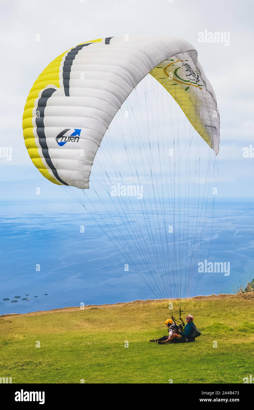 Arco da Calheta, Madeira, Portugal - Sep 16, 2019: Tandem paragliders landing on the cliffs above the Atlantic ocean. The blue seawater in the background. Paragliding, extreme sports. Stock Photo
