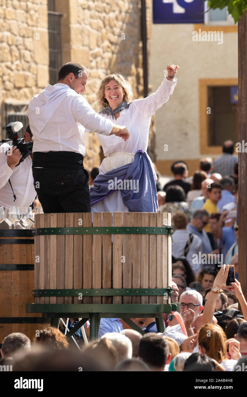 Rioja Alavesa wine harvest festival 2019 ceremonial stomping, crushing or treading of the grapes in traditional wooden vat - Bano de Ebro, Spain, Stock Photo
