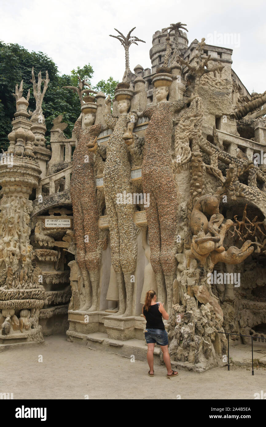 Visitor in front of the Ideal Palace (Le Palais idéal) designed by French postman Ferdinand Cheval and build from 1876 to 1912 in Hauterives, France. Roman dictator Julius Caesar, Celtic king Vercingetorix and Greek mathematician and physicist Archimedes are depicted from left to right as the Three Giants on the east facade.  ATTENTION: This image is a part of a photo essay of 36 photos featuring the Ideal Palace (Le Palais idéal). Stock Photo