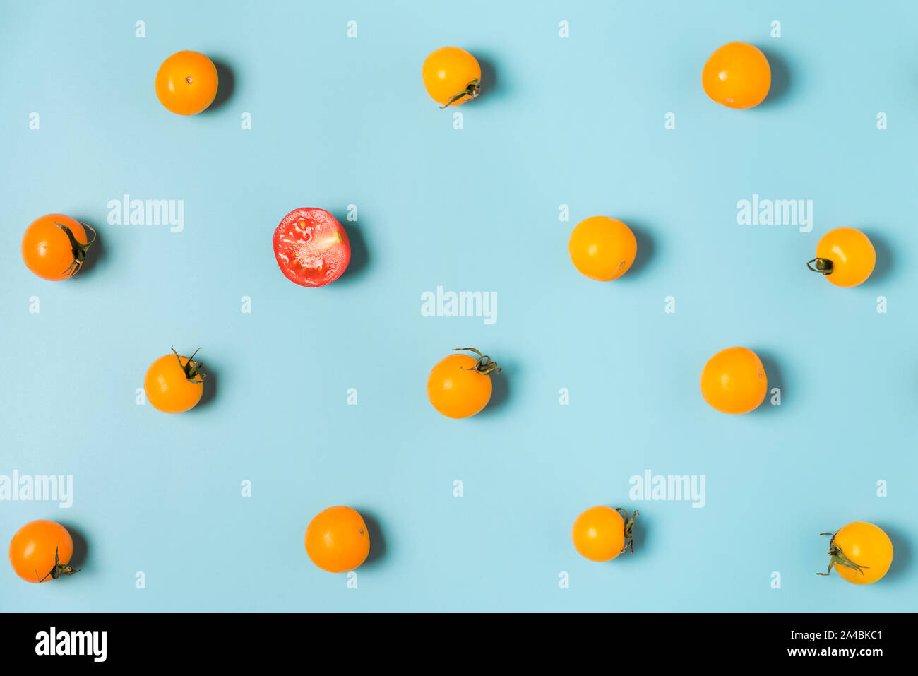 Half of red tomato cherry stand out from yellow tomatoes cherry. individuality and difference concept. flat lay Stock Photo