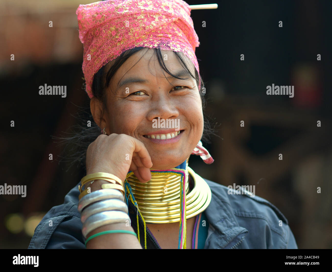 """Myanmarese Kayan Lahwi woman (""""giraffe woman"""") with tribal brass neck rings/coils smiles for the camera. Stock Photo"""