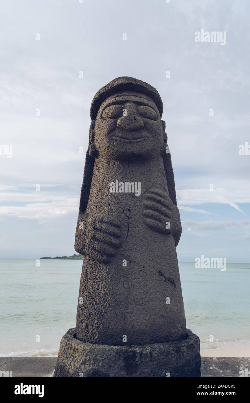Jeju Island, South Korea, september 05, 2019: View of one of the Dol Hareubang on Geumneung  beach with sea behind it Stock Photo