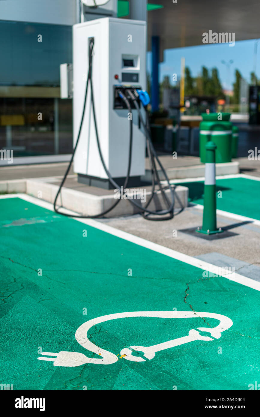 Electric charge station. Electric plug for charging cars. Car charging symbol painted on asphalt. Ecology fuell concept. Stock Photo