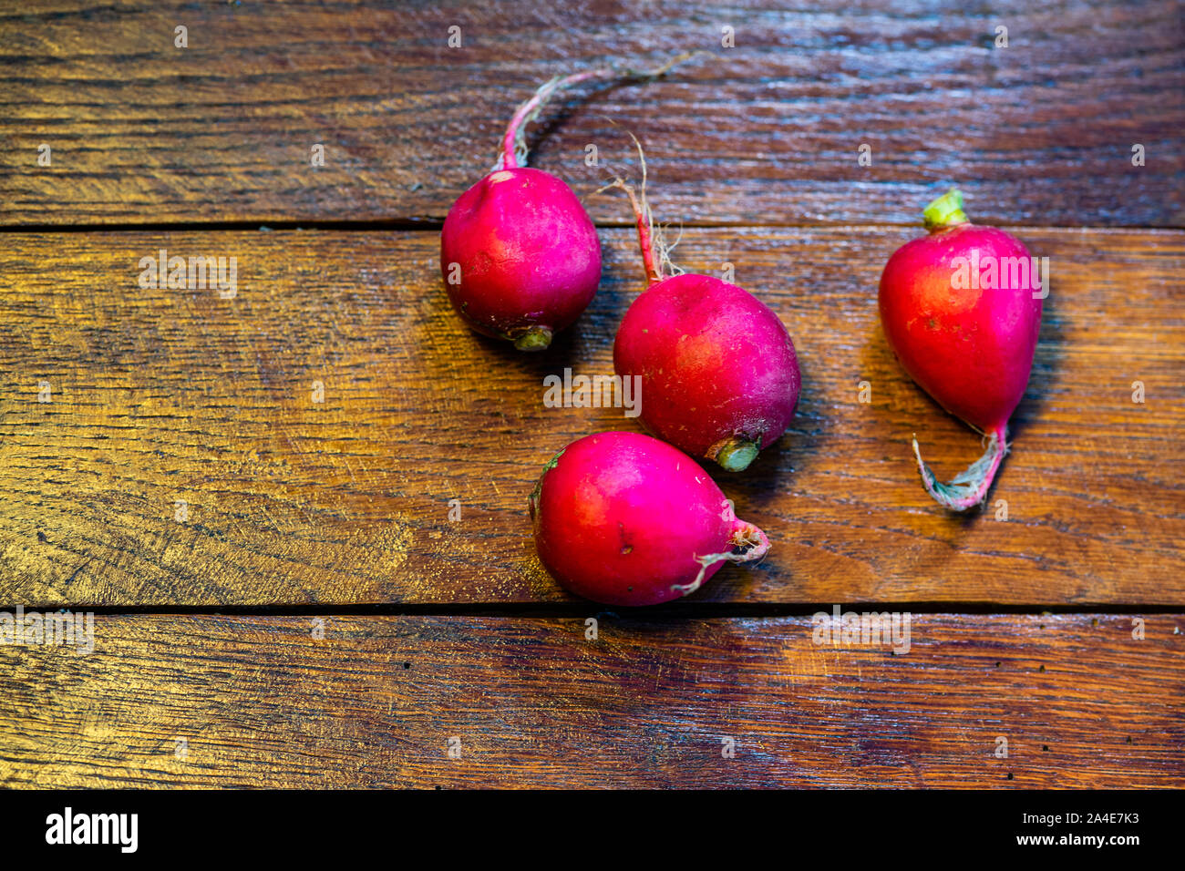 Fresh red radishes on a wooden board. Stock Photo